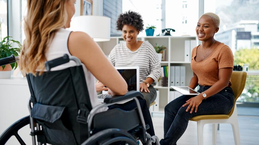 Shot of a businesswoman with disabilities sitting with colleagues in the office