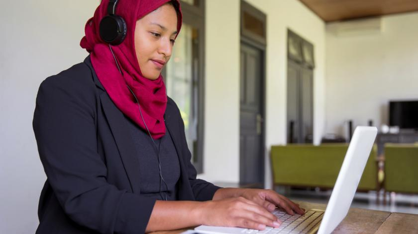 Portrait shot of Asian muslim teacher making online lessons on her laptop for students at home, during lockdown Covid 19