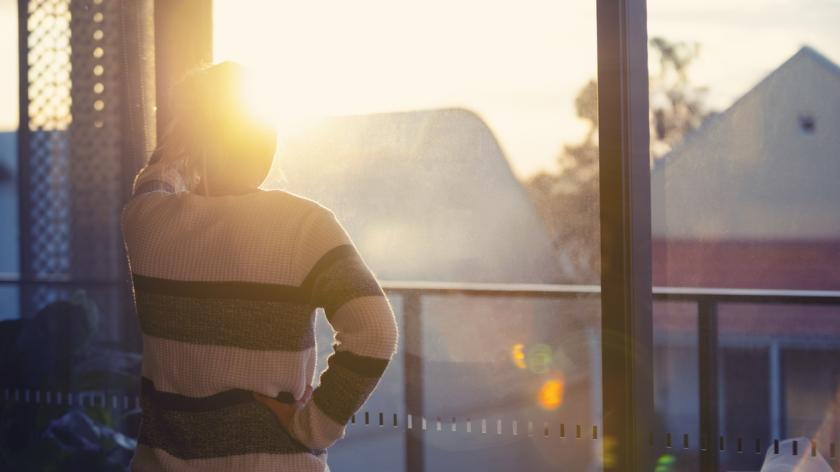 Woman looking through the window at sunset. She is alone and looks a little ad or depressed.