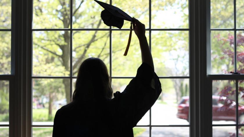 Graduate celebrating at home