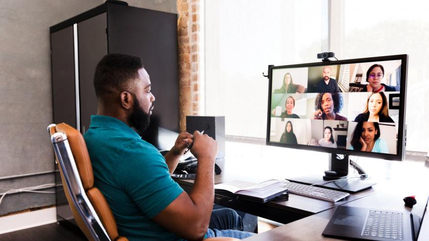 During COVID-19, a mid adult manager video conferences with his team.
