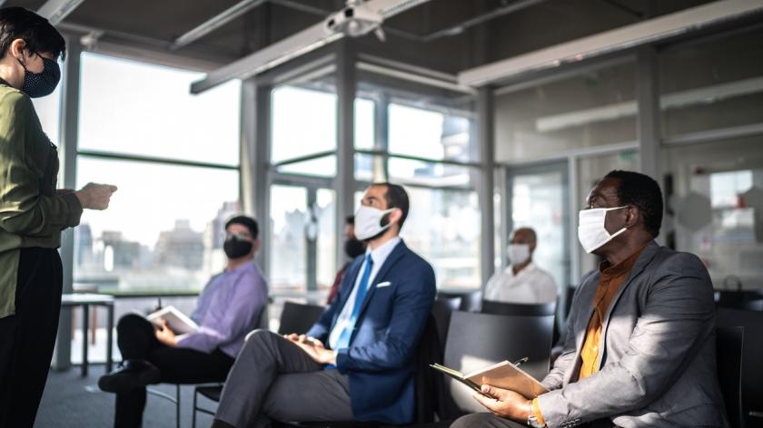 Business people attending a seminar with social distancing and face mask