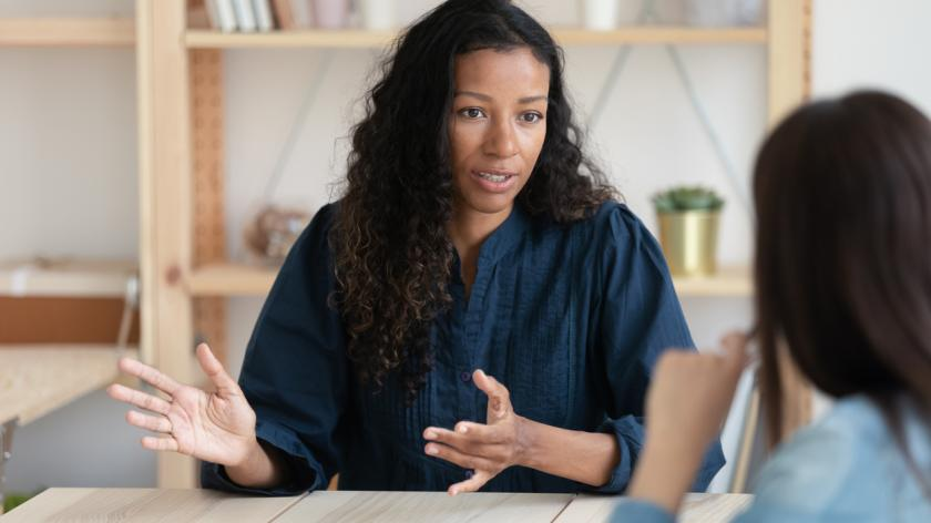 Close up confident african american businesswoman explaining new responsibilities to female applicant.