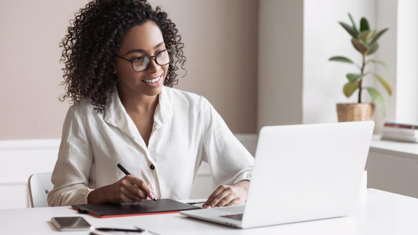Freelancer woman working on laptop computer at home.