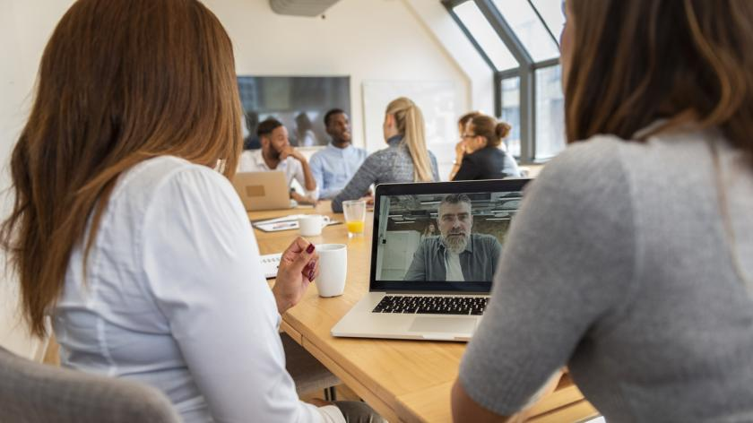Business team having a meeting in an office. They are using laptop for video conference. Coworkers are having a discussion.
