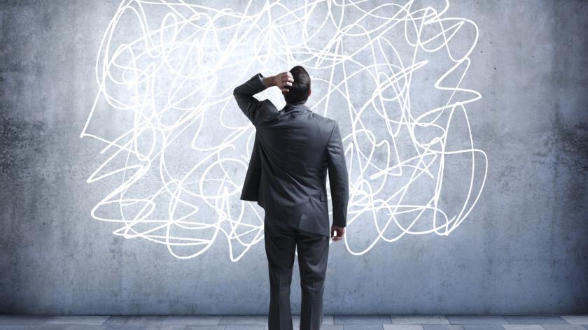 A confused businessman stares at a scribble design that is painted on a wall