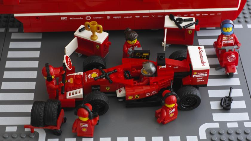 Lego team crew members are fixing wheel of Ferrari F14 T race car by LEGO Speed Champions. Studio shot.