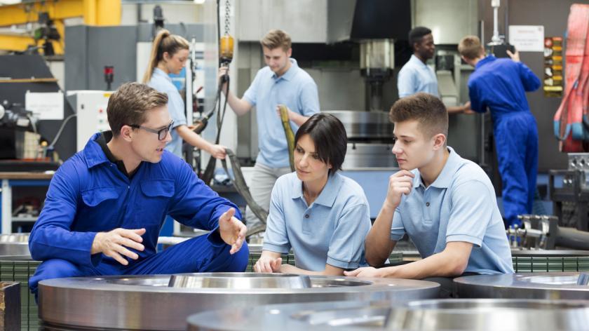 Three factory workers in workspace talking.