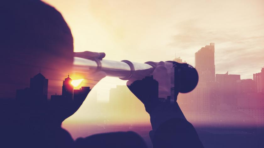 Man with telescope looking at city scape
