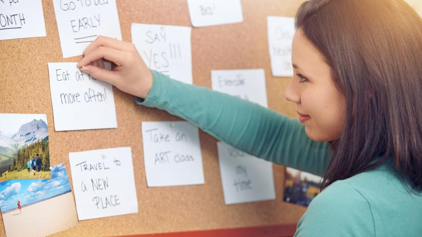 woman writing new year resolutions on a pin board