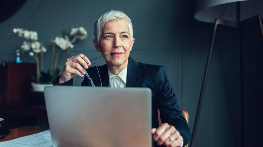 Portrait of mature businesswoman, sitting in her office and thinking. Holding eyeglasses in her mouth. In front of her on the desk is laptop.
