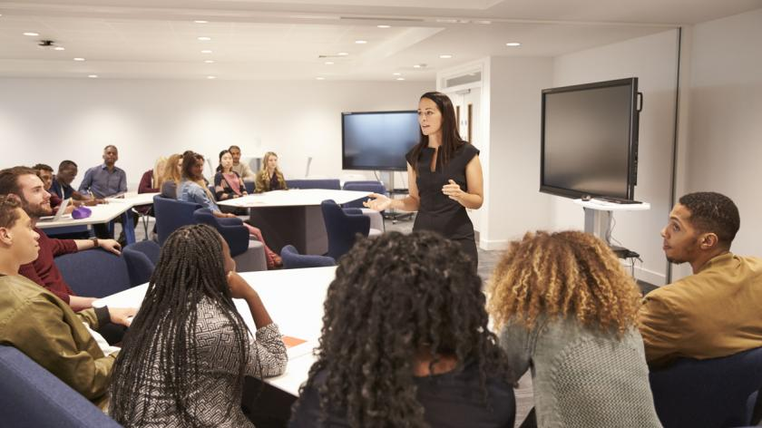 Female employee addressing colleagues in a classroom