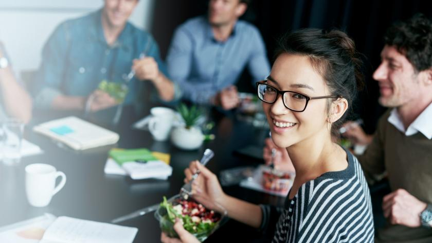 woman eating a salad in a work meeting