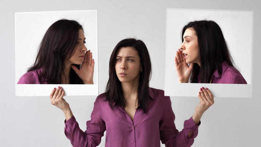 A girl holds two images of herself, both whispering into her ear