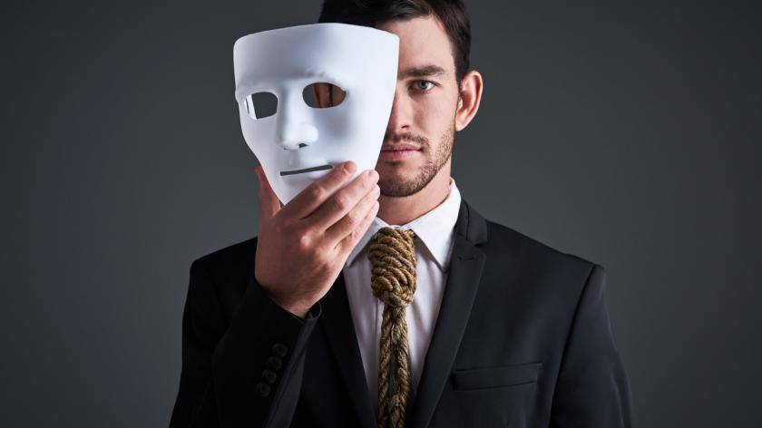 business man removing mask from his face
