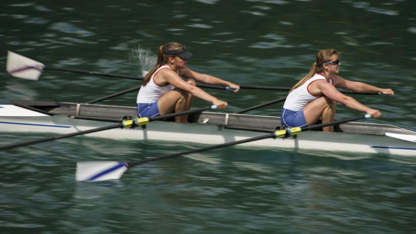 Two female rowers rowing across lake in late afternoon.