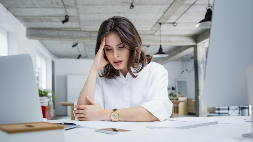 woman sitting at her desk looking upset