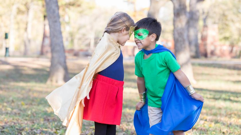 Elementary age boy and girl pretend to be superhero and villain.