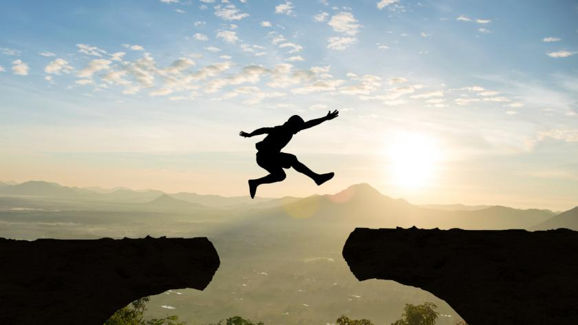 Man jumping over cliff