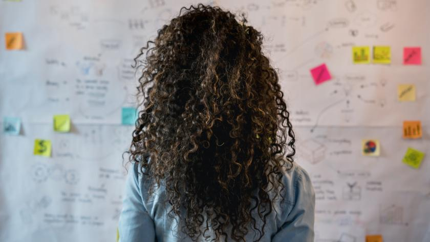 woman with her back to the camera looks at strategy board