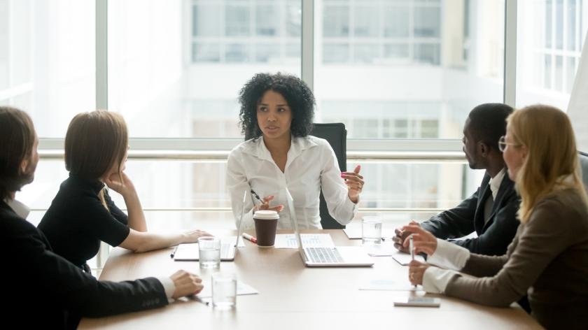 Female boss leading corporate meeting talking to diverse businesspeople