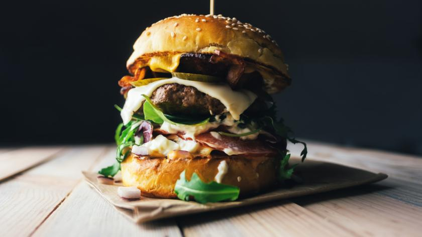 Appetizing cheeseburger on wooden table.