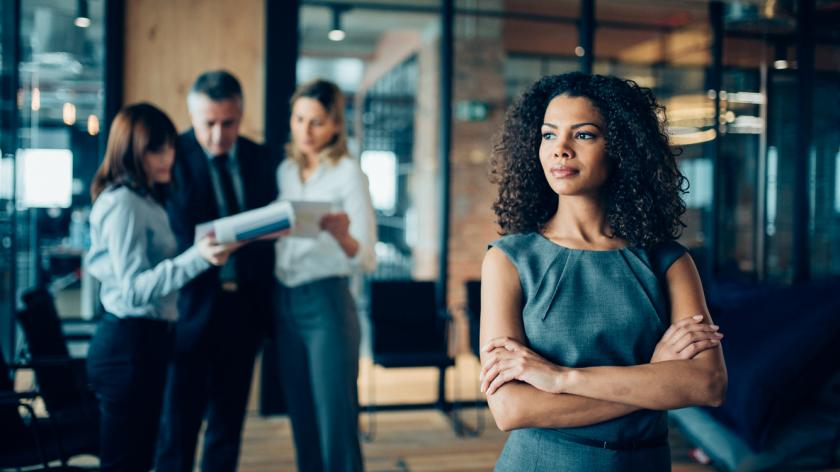Beautiful african-american ethnicity woman sitting confidently in office looking away