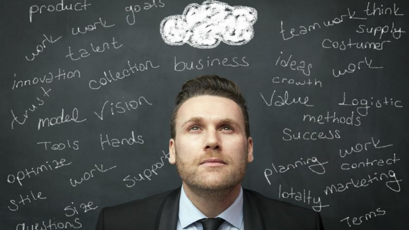 A man daydreaming in front of a blackboard