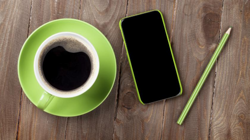a coffee cup, a pen and a smartphone
