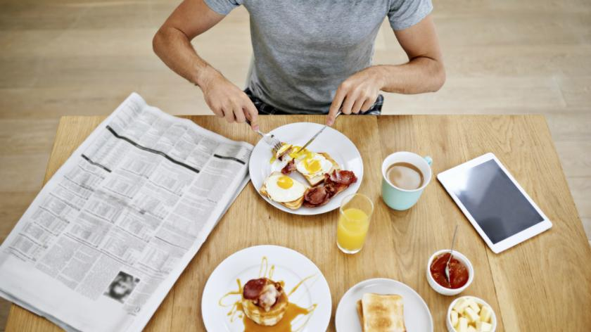 A man having breakfast while he reads the news