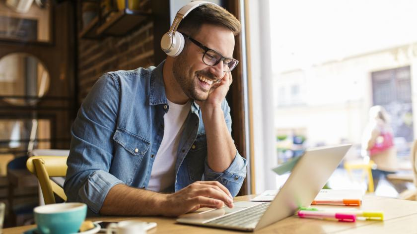 man working remotely in cafe