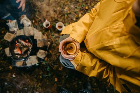 High angle view of a woman drinking mulled wine by the campfire; friends on an adventure in the woods, camping and enjoying a cup of warm mulled wine on a chilly night.